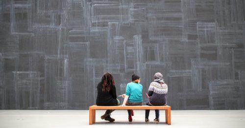 Drei Menschen auf einer Bank sitzend vor einer grauen Wand. Foto: © CCO