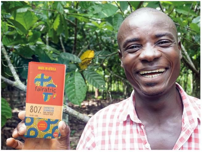 Kakaobauer mit Fairafric Schokolade auf einer afrikanischen Kakaoplantage. Foto: © Fairafric