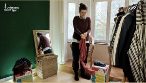 Ein Screenshot des Anti-Konsumrausch-Videos, auf dem sich eine weibliche Person viele Kleidungsstücke in Schichten anzieht.