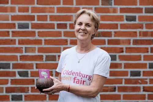 Frau in T-Shirt mit dem Logo von Oldenburg handelt fair und fairer Schokolade in den Händen. Foto: © J. Bädeker