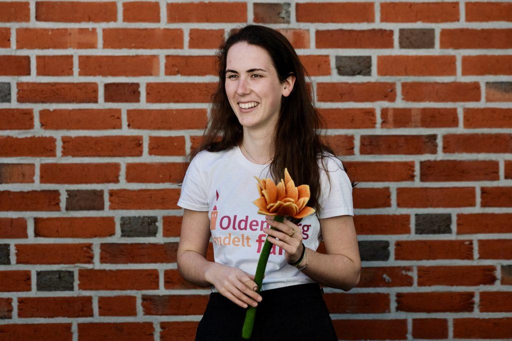 Mädchen in T-Shirt mit dem Logo von Oldenburg handelt fair und einer Filzblume in der Hand. Foto: © J. Bädeker