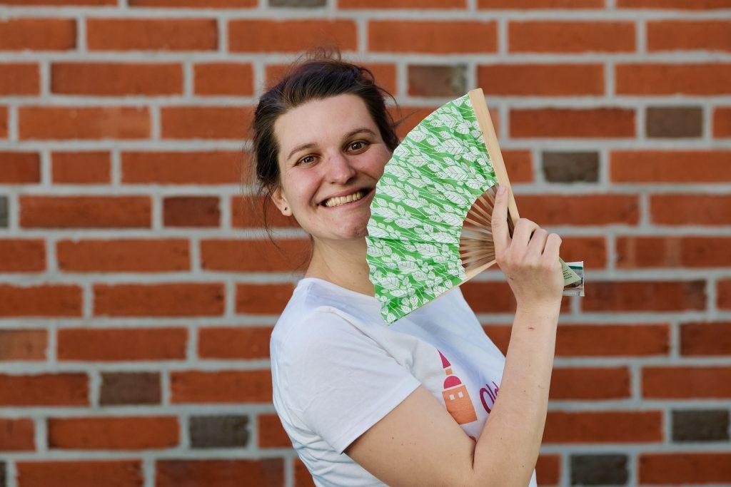 Mädchen in T-Shirt mit dem Logo von Oldenburg handelt fair und einem Fächer in der Hand. Foto: © J. Bädeker