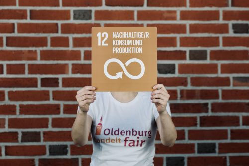 """Person im T-Shirt von """"Oldenburg handelt fair"""" mit dem Schild zu SDG 12; Foto: © J. Bädeker"""