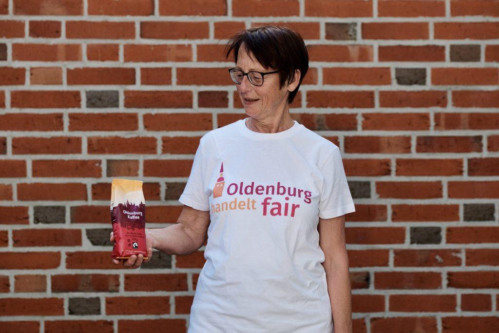 Frau in T-Shirt mit dem Logo von Oldenburg handelt fair und Oldenburg Kaffee in den Händen. Foto: © J. Bädeker