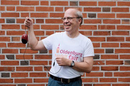 Mann in T-Shirt mit dem Logo von Oldenburg handelt fair und einer Computermaus in den Händen. Foto: © J. Bädeker