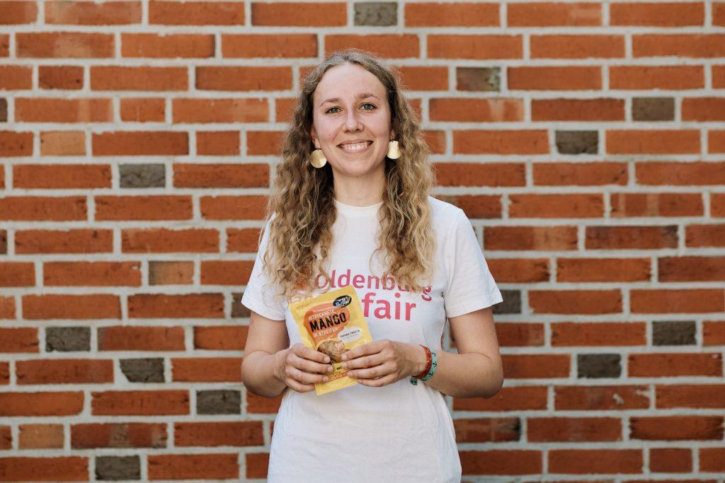 Mädchen in T-Shirt mit dem Logo von Oldenburg handelt fair und getrockneten Mangostreifen in der Hand. Foto: © J. Bädeker