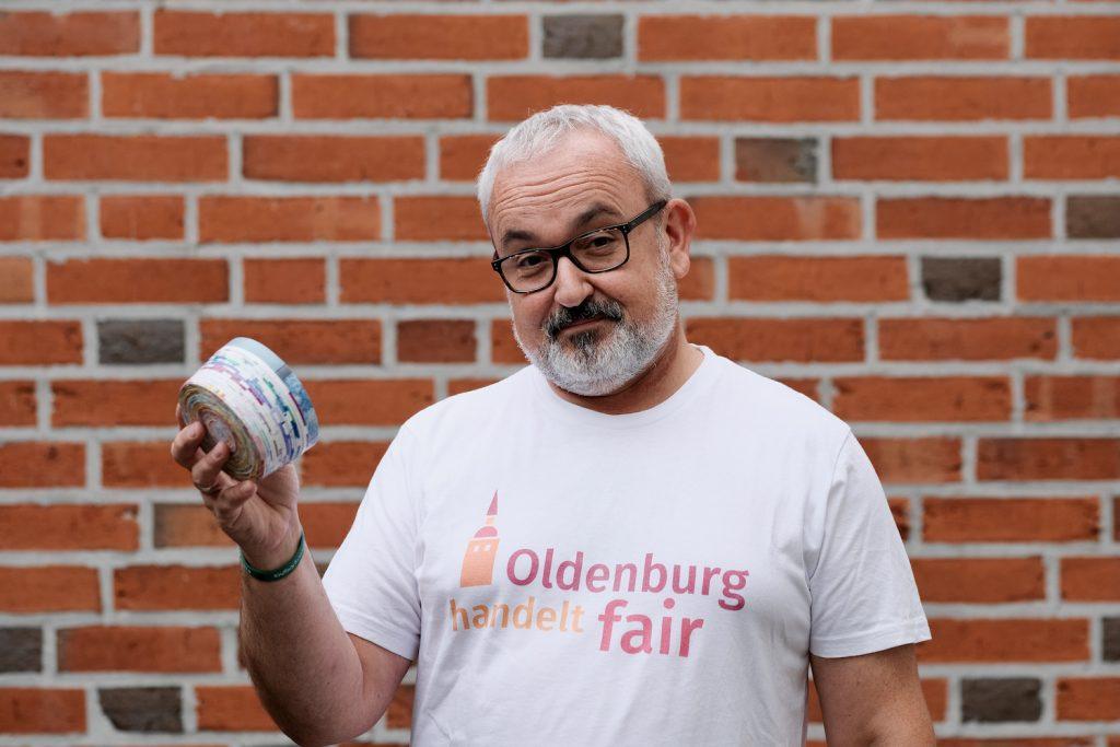 Mann in T-Shirt mit dem Logo von Oldenburg handelt fair und nachhaltiger Dose in den Händen. Foto: © J. Bädeker