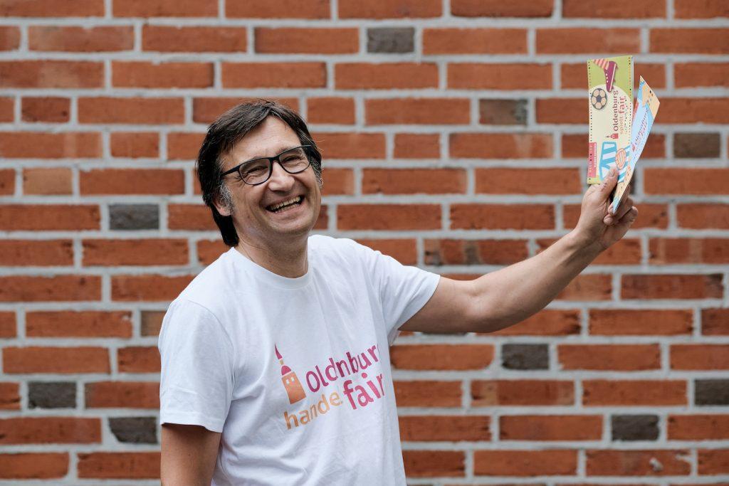 Mann in T-Shirt mit dem Logo von Oldenburg handelt fair und Oldenburg Fair Flyer in den Händen. Foto: © J. Bädeker