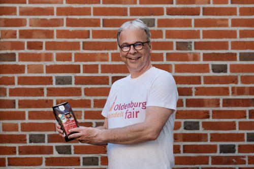 Mann in T-Shirt mit dem Logo von Oldenburg handelt fair und Bio-Kaffee in den Händen. Foto: © J. Bädeker