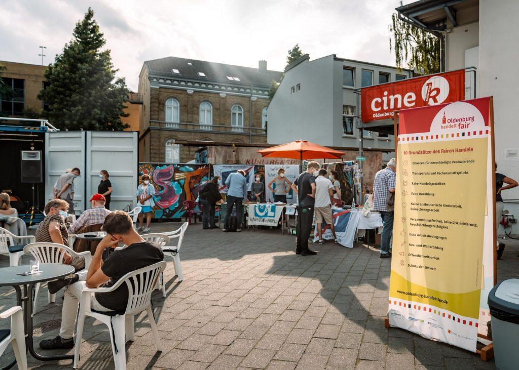 """Buntes Treiben auf dem Draußenbereich des Cine ks beim Draußenkino. Besonders sticht der Banner von """"Oldenburg handelt fair"""" hervor."""