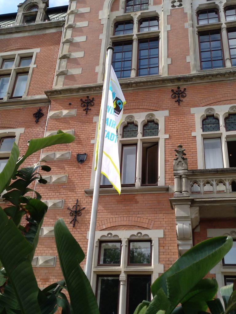 Die Flagge zur Rezertifizierung der Stadt Oldenburg als Fairtrade Stadt hängt im Zeitraum der bundesweiten Fairen Woche vor dem Rathaus.