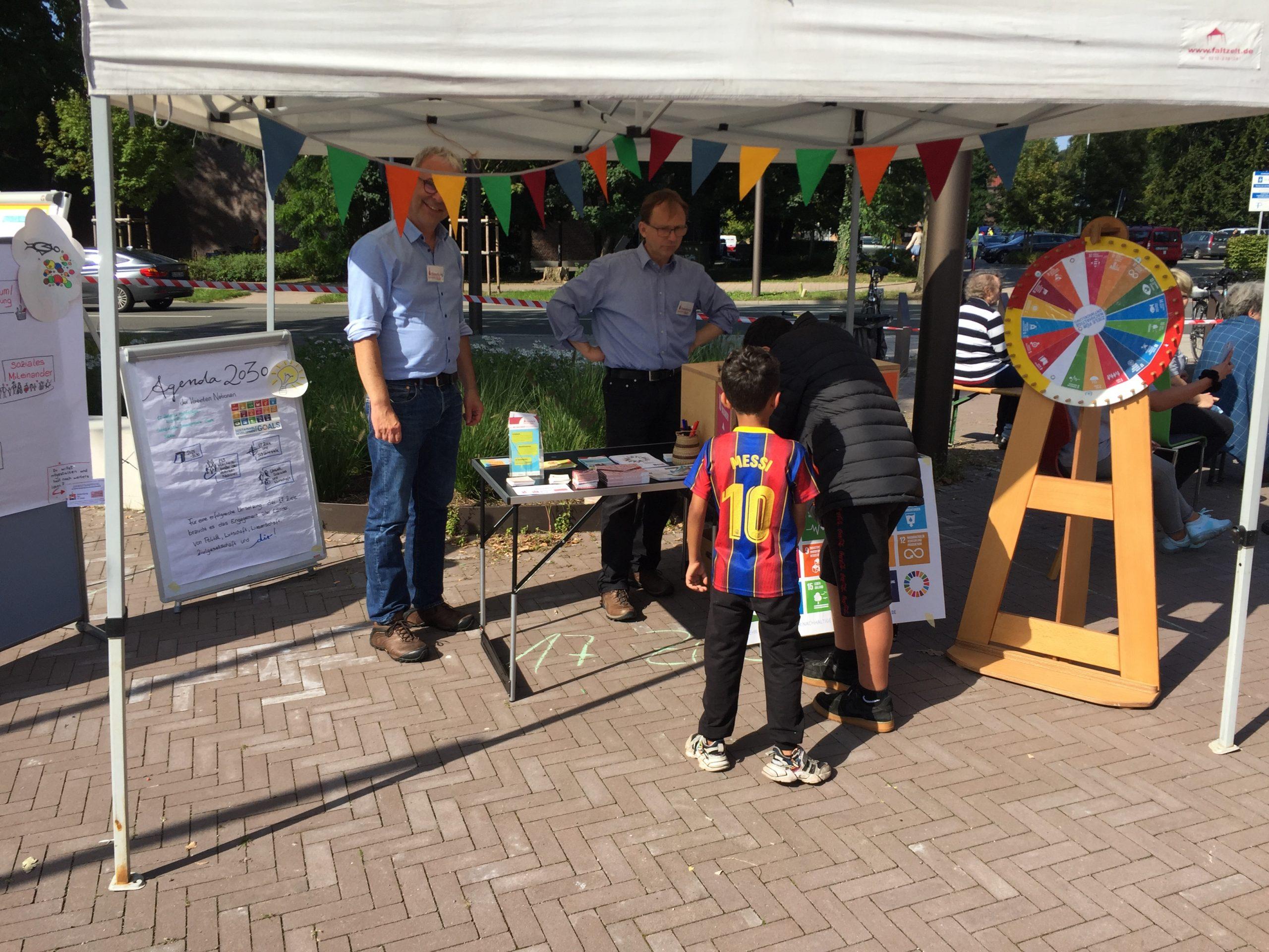 Zwei Kinder sind von hinten am Stand der SDG-Werkstatt in Kreyenbrück auf dem Stadtteilfest zu sehen.