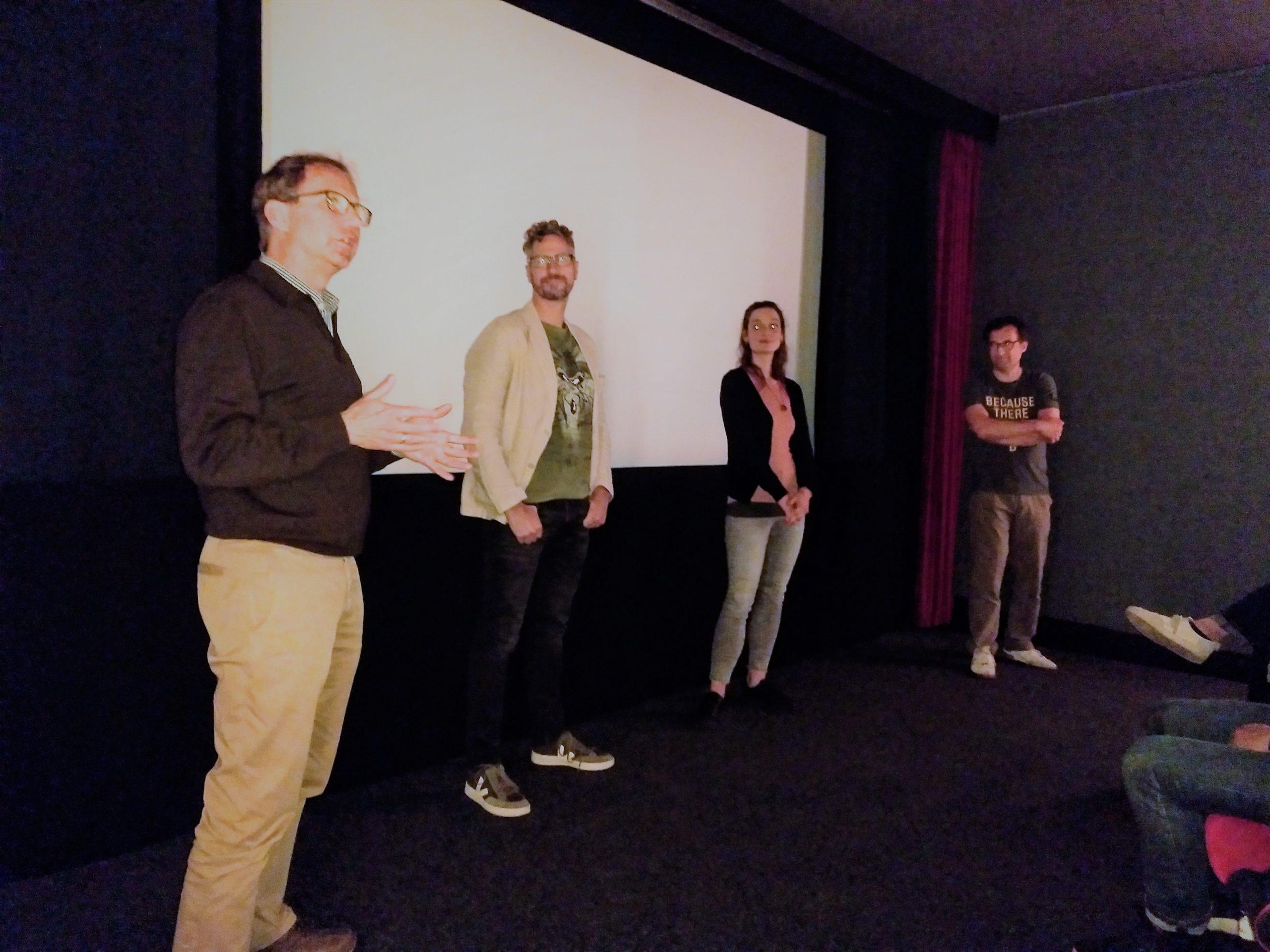 Vier Personen sind im Muvi-Saal des Cine-k vor der Leinwand zu sehen, die miteinander im Gespräch sind.